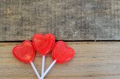 Red Heart shaped lollipops on wood backdrop