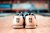 stock photo of bowling ball  - Bowling footwear. Close up of bowling shoes lying on bowling alley