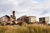 picture of sugar industry  - Close view of old deserted sugar mill being overgrown by nature near Koloa Kauai in Hawaii - JPG