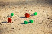 image of beach-house  - Small red and green plastic houses in the sand on the beach - JPG