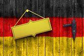 golden plate on a wooden door with german flag