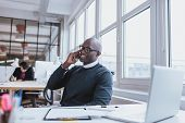 stock photo of people talking phone  - Young man talking on his mobile phone in office - JPG