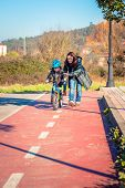 Mother teaching son to ride a bike in cycleway