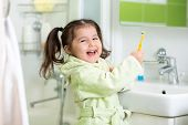 stock photo of little kids  - Kid little girl brushing teeth in bath - JPG