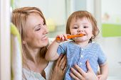 picture of teething baby  - smiling mother and kid son brushing teeth in bathroom - JPG