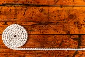 stock photo of coil  - Coiled white rope on a highly textured wooden background - JPG