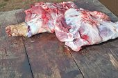 stock photo of slaughter  - Pieces of pig over wooden table - JPG
