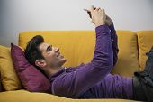 stock photo of memento  - Sexy handsome young man sitting indoors posing for a selfie on his mobile phone smiling for the camera - JPG