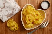Raw tagliatelle in a heart shaped bowl