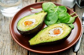 pic of continental food  - avocado baked with egg on a dark wood background - JPG