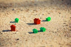 picture of social housing  - Small red and green plastic houses in the sand on the beach - JPG