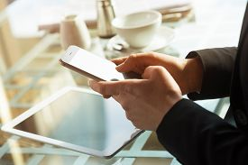 image of touching  - Businesswoman at the bar text messaging with her mobile touch screen phone hands close up - JPG
