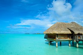 foto of french polynesia  - Luxury thatched roof honeymoon bungalow in a vacation resort in the clear blue lagoon of the tropical island of Bora Bora near Tahiti in French Polynesia - JPG