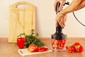 stock photo of blender  - Hands cooks are going to chop red pepper in a blender - JPG