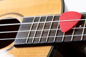stock photo of musical instrument string  - Small Hawaiian four stringed ukulele guitar with red pick between strings closeup - JPG
