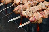 stock photo of brazier  - The shish kebab on skewers is fried on a brazier - JPG