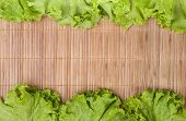 stock photo of bamboo leaves  - lettuce leaves laid on both sides on a bamboo table cloth - JPG