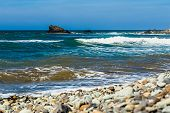 pic of atlantic ocean  - Wild stone beach and rock in water on coast or shore of the Atlantic ocean with waves and sky with clouds and skyline or horizon in Tenerife Canary island Spain at spring or summer - JPG