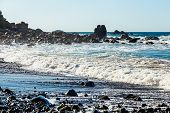 pic of atlantic ocean  - Waves and foam on wild stone beach on coast or shore of the Atlantic ocean with sky and rock on skyline or horizon in Tenerife Canary island Spain - JPG