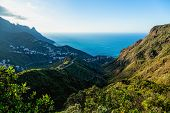 picture of atlantic ocean  - City or village and winding or serpantine road in green mountain or rock valley and clouds with horizon landscape near coast of Atlantic ocean in Tenerife Canary island Spain - JPG