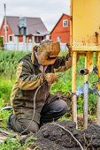 picture of pipe-welding  - Welder with mask soldering pipe outdoor in countryside - JPG