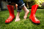 stock photo of lady boots  - Closeup photo of barefoot girl standing on grass with red rubber boots - JPG
