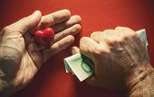 image of holding money  - Conceptual composition about love or money two male hands one holds money tightly and other red heart as symbol of love - JPG