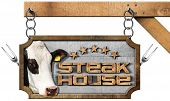 foto of food chain  - Wooden and metallic sign with text Steak House five stars head of cow and forks - JPG