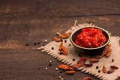 pic of chillies  - chilli sauce in a cute little bowl on a wooden table - JPG
