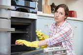 stock photo of spring-cleaning  - Portrait Of Fed Up Woman Cleaning Oven