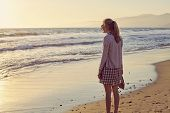 picture of loafers  - Young blonde woman in glasses and plaid dress with shoes in hand walking barefoot on wet sand of misty beach - JPG