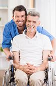stock photo of male nurses  - Male nurse talking with senior patient in wheelchair - JPG