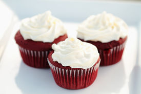 image of red velvet cake  - Three red velvet cupcakes on a white dish with extreme shallow DOF.