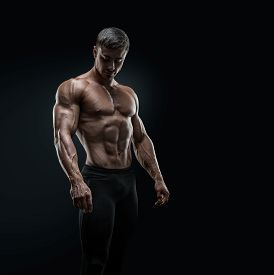 picture of cardiovascular  - Muscular and fit young bodybuilder fitness male model posing over black background - JPG