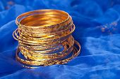 Thin Gold Bangles Put On A Blue Textile