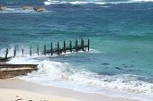 Wooden pier on beach with choppy blue seas