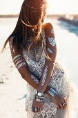 Beautiful girl wearing bohemian chic clothing with flash tattoo on her body posing on the shore in s poster