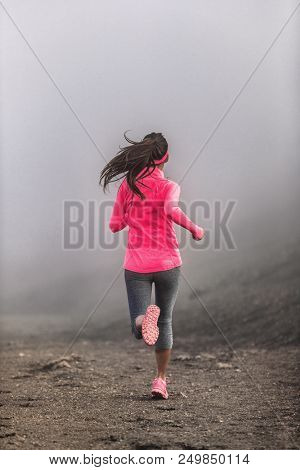 poster of Run fit woman runner running on trail path in mountains in fog and clouds - morning jogging training
