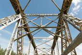 Metal Bridge Against Bright Blue Sky. Infrastructure And Architecture poster