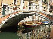 Pretty canal with reflections of boats and bridge in Venice, Italy