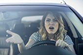 Angry Woman Driving A Car. The Girl With An Expression Of Displeasure Is Actively Gesticulating Behi poster