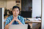 Portrait Of A Focused Young Asian Designer Sitting At His Workstation While Working Late In A Modern poster