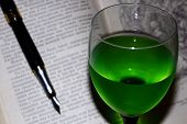 Absinthe In A Glass, On The Background Of A Fountain Pen, And An Open Book poster