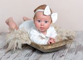 Adorable newborn baby girl with headband lying on fluffy rug and looking aside with curiosity. Cute  poster