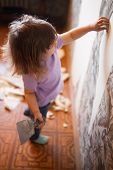 Adorable Little Girl Repairing Wall In Apartment, Holding Putty Knife Old Wall At The Background. Co poster