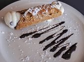 Italian Pastry Dessert, Cannoli Dusted With Powdered Sugar And Chocolate Sauce.  The Filling Is Swee poster