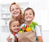 Happy family with the grocery bag full of fresh vegetables - healthy life concept