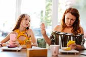 Busy Mother. Red-haired Working Mother Feeling Extremely Busy While Spending Time With Daughter poster
