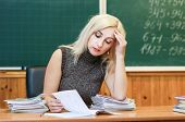 A Pretty Teacher Holds Her Head In Her Hands And Checks The Test Papers. A Hard Day Of The Teacher.  poster