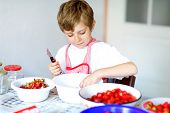 Little Blond Kid Boy Helping And Making Strawberry Jam In Summer. Funny Child Cleaning Berries And P poster